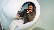 """Liegt gut in der Kurve: Designer Luigi Colani demonstriert 1995 in Köln ein Sitzmöbel für seine Wohneinheit """"Habitaner""""."""