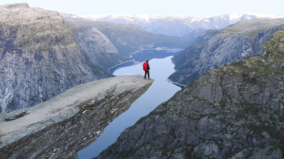 Bitte beachten Sie nicht die dreihundert Influencer, die noch hinter mir stehen: Auf der Trolltunga über dem norwegischen Ringedalsvatnet-See ist man nur noch selten allein.