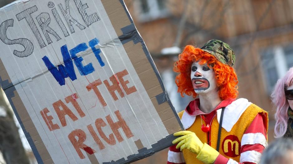"""Löst das Welthunger-Problem auch nicht: Ein als Ronald McDonald verkleideter Demonstrant fordert an Eröffnungstag des Weltwirtschaftsforums in Davos, """"Eat the Rich""""."""