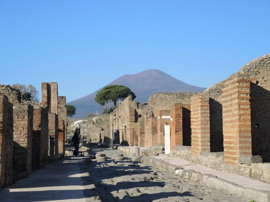 Blick in eine Straße Pompejis, die teils mit wiederverwendetem Baumaterial von den Friedhöfen der Stadt errichtet wurde. Im Hintergrund ist der nahe Vesuv zu sehen.