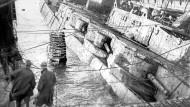 """Am 21. Juni 1919 versenkte die Besatzung der nach dem Waffenstillstand in der schottischen Bucht von Scapa Flow festgesetzten deutschen Hochseeflotte ihre Schiffe, um sie nach der bevorstehenden Unterzeichnung des Friedensvertrags nicht übergeben zu müssen. Hier wird von Briten der Schlachtkreuzer """"Hindenburg"""" wieder gehoben."""