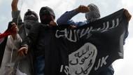 Vermummte Demonstranten halten eine Fahne des IS hoch.
