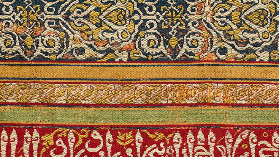 Die Seide spricht: Streifenstoff mit arabischer Inschrift Granada, 14. Jahrhundert. Die weiße Inschrift auf leuchtend rotem Grund hebt an mit den Worten Hier spricht das Gewebe: Ehre für unseren Herrscher, den Sultan! - es handelt sich dabei um Verse aus einem poetischen Lobes- und Liebesgedicht, die in einer schwungvollen arabischen Kursivschrift geschrieben sind.