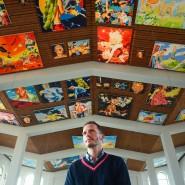 """Der Künstler Norbert Bisky steht in der St.-Matthäus-Kirche vor den Bildern seiner Ausstellung """"POMPA"""" an der Decke des Kirchenbaus."""