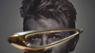 Ein David Bowie-Porträt, und im Vordergrund eine goldene Skulptur von Denis Mitchell. Sie steht zum Verkauf.