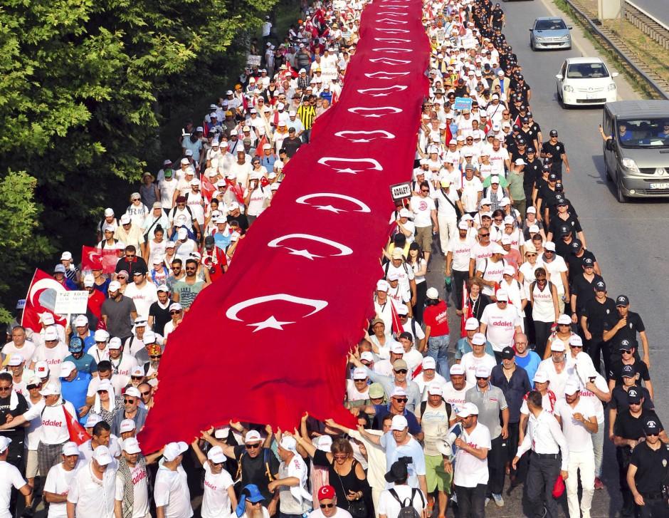Inzwischen haben sich Tausende auf dem Weg gemacht. Die hier mitgeführte türkische Flagge ist 1111 Meter lang.