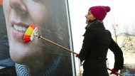 Die Mütze passt zur neuen Werbefarbe: Katja Suding bürstet die letzten Falten eines Wahlplakats aus.