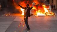 Normalität? Auf der Place de la Republique in Paris posiert am Dienstag ein Demonstrant vor einem brennenden Polizeifahrzeug.