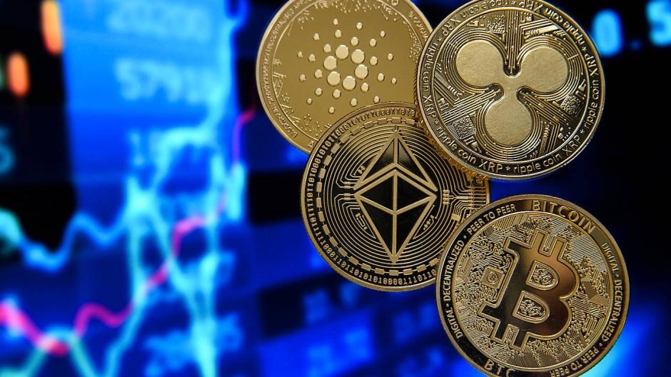 Münzen als Symbole für die Kryptowährungen Bitcoin, Ether, Ripple und Cardano