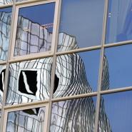 Das Logo der Deutschen Bank spiegelt sich an einer Fassade.