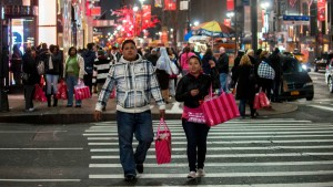 People carry shopping bags as they walk through Herald Square in New York