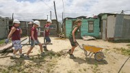 """""""Voluntourism"""" heißt die Kombination aus Freiwilligenarbeit und Tourismus. Die vier Jugendlichen bauen Häuser im südafrikanischen Kapstadt."""