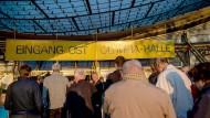 Teilnehmer der Gläubigerversammlung im Millardenbetrugsfall P&R stehen an der Olympiahalle im Olympiapark.
