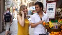 Ein junges Paar telefoniert entspannt aus dem Urlaub - die Auslandsgebühren fallen ab Samstag deutlich.