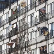 Schön ist etwas anderes: Eine Vielzahl an Satellitenschüsseln, die an die Balkone eines Hauses montiert sind.