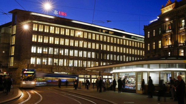 A tram drives past the building of Swiss banks UBS and Credit Suisse at the Paradeplatz in Zurich