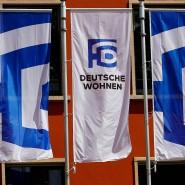 Unternehmensflaggen wehen vor einem Bürogebäude von Deutsche Wohnen.
