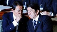 Finanzminister Aso (l) spricht, Ministerpräsident Abe (r) hört's nicht gerne