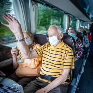 Nur noch mit Maske: Passagiere winken aus einem Reisebus