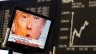 Viele Amerikaner investieren in Deutschland: Donald Trump vor einer Anzeigetafel mit dem Dax-Kurs.