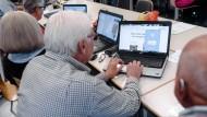 Senioren nehmen in Hamburg an einem Computerkurs der Volkshochschule teil.