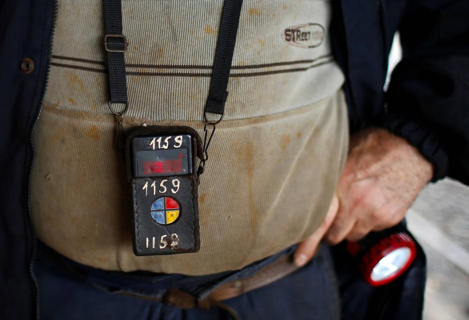 Ein  Bergmann trägt einen Gasdetektor, der ihn unter Tage vor dem gefährlichen Grubengas warnen soll.