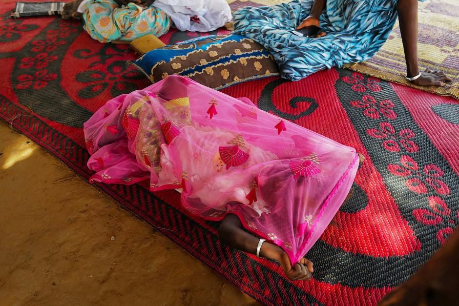 Ein Mädchen spielt mit einem Schal im Haus ihrer Familie.