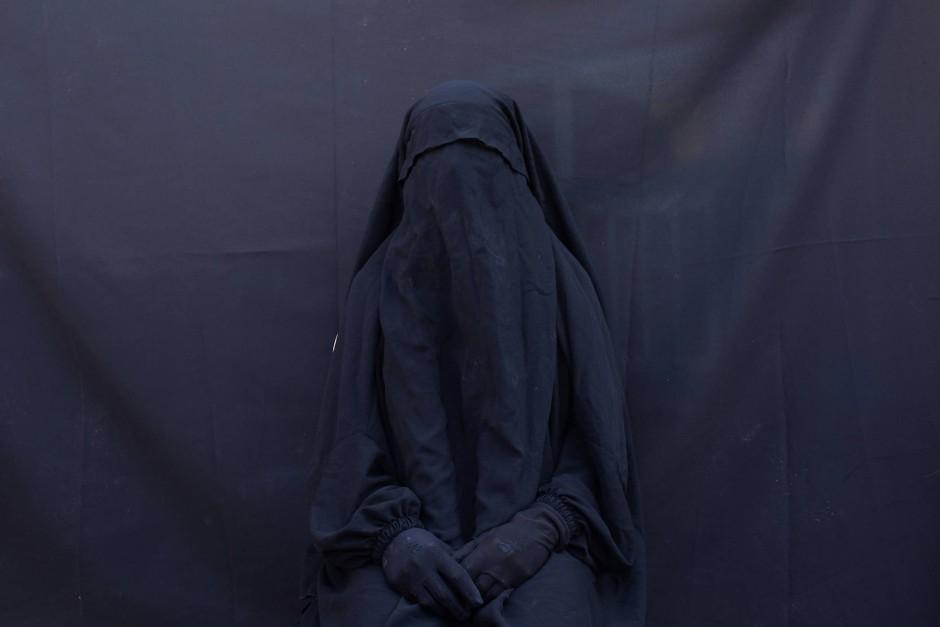 Die Jesidin Layla Taloo posiert für ein Porträt in ihrer Wohnung im Irak. Den Gesichtsschleier und die Abaya trug sie auch während der zweieinhalb Jahre, in denen sie von Mitgliedern des Islamischen Staats versklavt wurde.