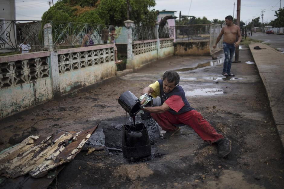 Selbsthilfe, wo der Staat versagt: Einwohner versorgen sich aus einer undichten Pipeline mit Rohöl.