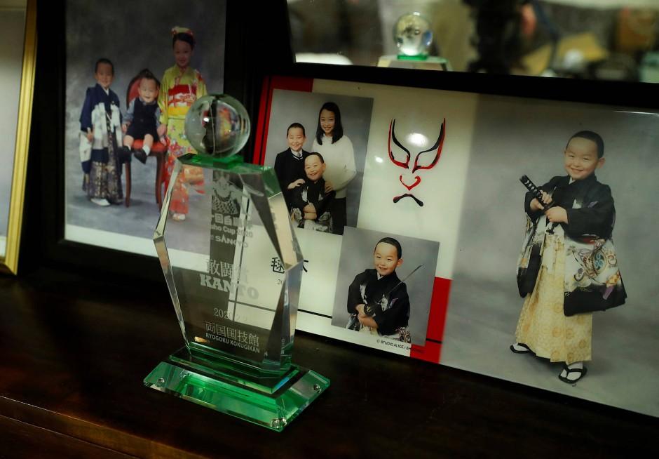Eine Trophäe des Hakuho Cups steht neben Familienfotos von Kyuta.