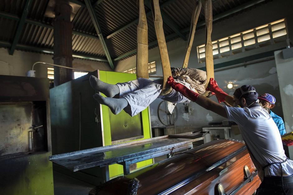 Mitarbeiter eines Friedhofs bereiten eine Leiche für die Einäscherung vor.