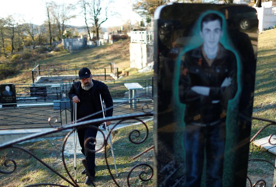 """Guram Gamezardashvili steht am Grab seines Sohnes Pavle, der bei dem Grubenunglück in der Mindeli-Mine ums Leben kam. Der 54 Jahre alte Bergmann Guram wurde 2010 bei der Arbeit in der Mine verletzt und ist seitdem im Ruhestand. Sein Sohn Pavle starb Anfang 2018 in der Mine. """"Es gibt keine andere Arbeit in der Stadt, deshalb arbeiten wir alle in der Mine. Wir brauchen mehr Aufmerksamkeit von der Regierung, die Sicherheitsregeln müssen verschärft werden. Die Schließung der Mine ist keine Lösung, dies würde nur zu mehr Arbeitslosigkeit und Hunger führen"""", sagt er."""