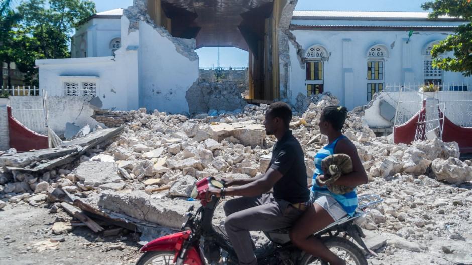 Menschen fahren am 15. August an einer zerstörten Kirche in Les Cayes vorbei.