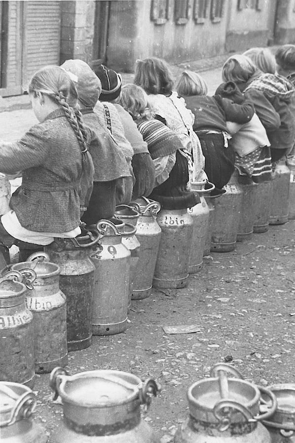Die lange Reihe der auf Milchkannen sitzenden Mädchen aus Albig, die an der Sammelstelle darauf warteten, dass ihre Ware abgeholt und in die Armsheimer Molkerei gebracht wurde