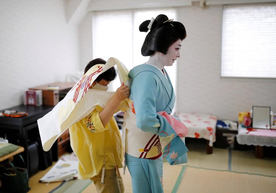 Koiku bekommt Hilfe beim Anziehen ihres Kimonos.