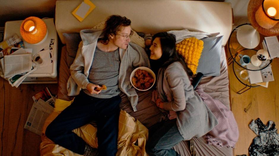 Hühnchen-Snack im Bett: Dieses Paar gönnt sich den Imbiss im Auftrag der Bundesregierung, um dafür zu werben, in der Pandemie zuhause zu bleiben.