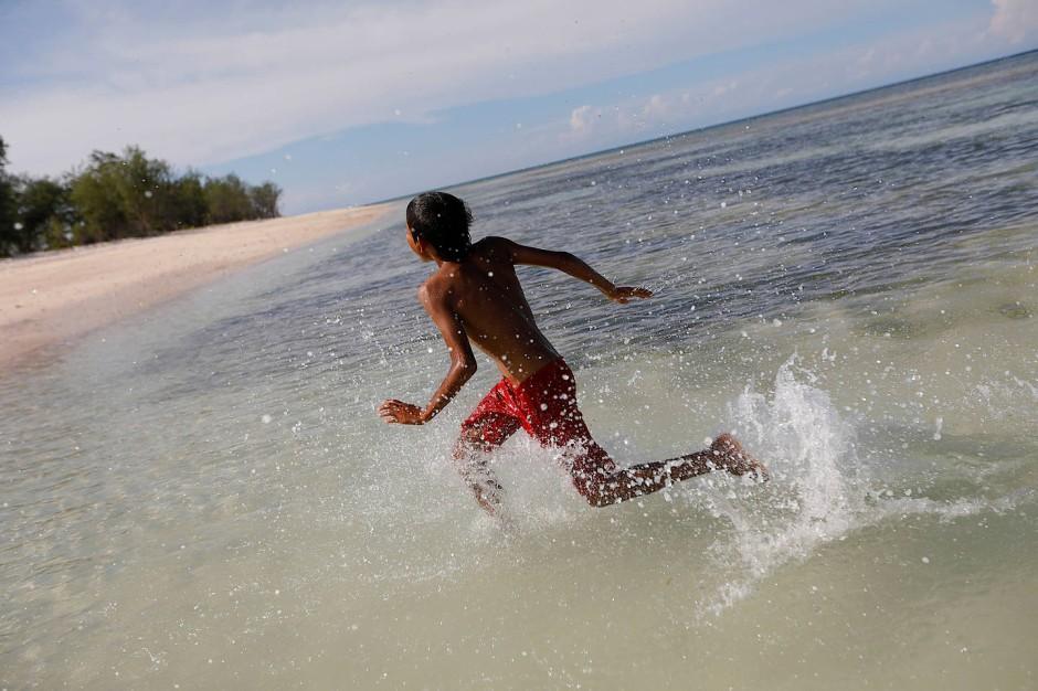 Dimas Mbaha Konda Lura spielt im Meer und wartet darauf, mit seinem Vater Ndelu Ndaha am Strand von Puru Kambera angeln zu gehen.