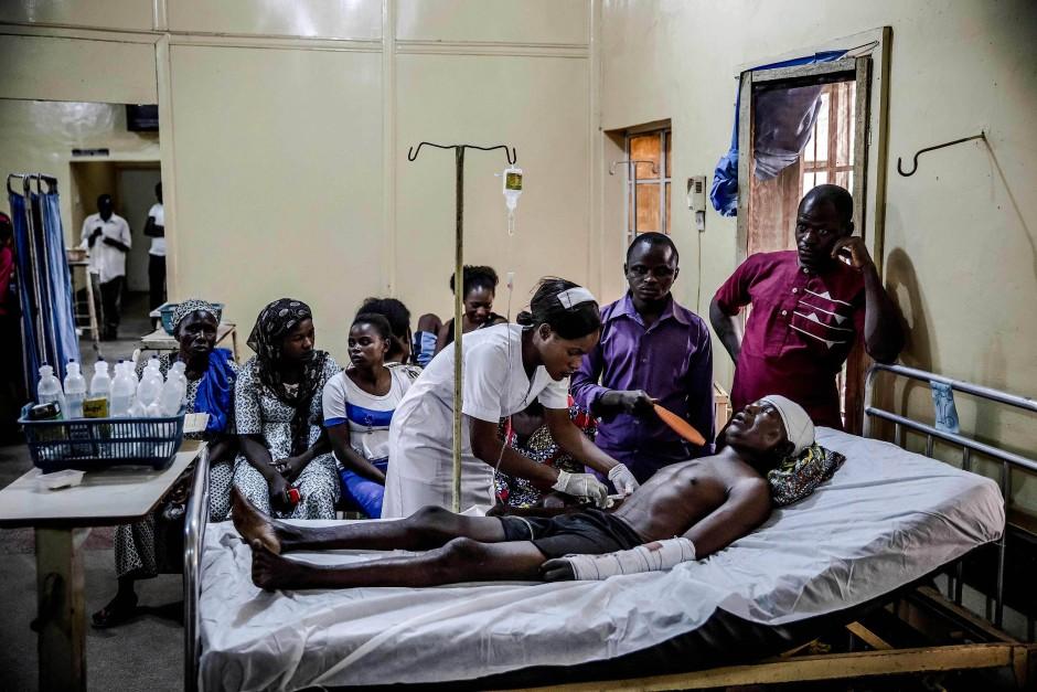 Ein Adara-Bauer, der bei einem Angriff der Fulani verletzt wurde, wird in der Obhut seiner Familie im Hospital von Kaduna versorgt.