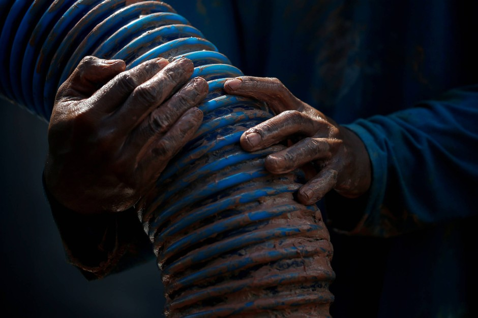 Ein Arbeiter hält den Schlauch, mit dem der zinnhaltige Sand aufgesaugt wird.
