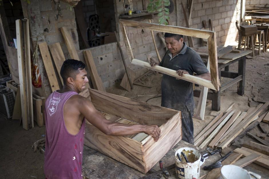 Sergio Morales und Joelvis Cantillo bauen einen einfachen Sarg in ihrer Möbelwerkstatt in Maracaibo, Venezuela. Die Nachfrage nach günstigeren Särgen stieg enorm. Deshalb begannen die beiden Schreiner vor zwei Jahren mit dem Bau von Särgen für weniger als 100 Dollar.
