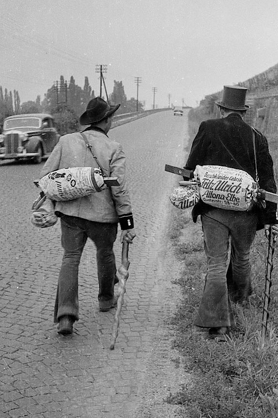 Auf der Walz - Zwei Zimmerleute während ihrer Wanderjahre im Januar 1957, aus Nackenheim kommend, in Richtung Nierstein laufend. Während ihrer Wanderschaft sollten sie vor allem neue Arbeitspraktiken, fremde Orte, Regionen und Länder kennenlernen sowie Lebenserfahrung sammeln. Eine alte Tradition ihrer Zunft, die sie oft durch ganz Europa führte.