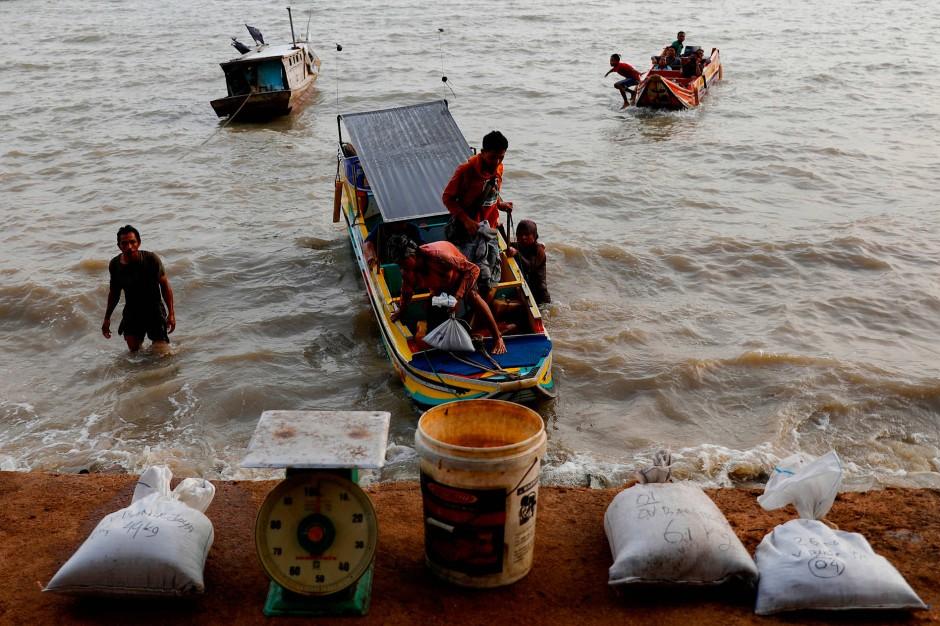 Arbeiter entladen Säcke mit zinnhaltigem Sand. Am Strand von Toboali wird er gesammelt und gewogen.