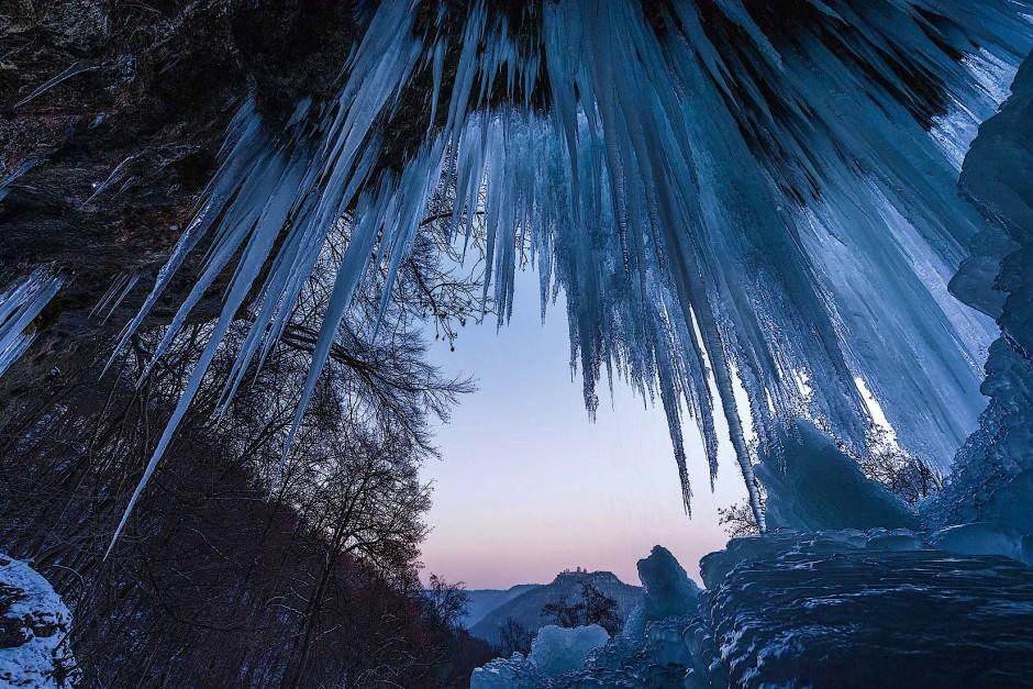 Der Uracher Wasserfall friert nur in extrem kalten und langen Kälteperioden nahezu komplett zu. An klaren Abenden gibt er unter seinen langen Eiszapfen diesen einmaligen Blick auf die Ruine Hohenurach frei.