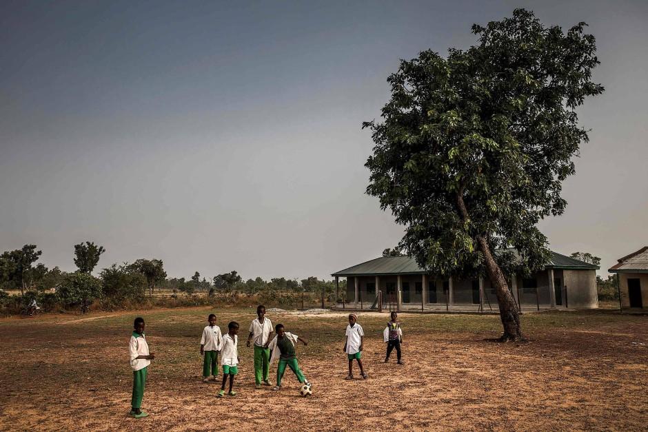 Fulani-Jungen spielen auf dem Schulgelände Fußball, bevor der Unterricht beginnt.