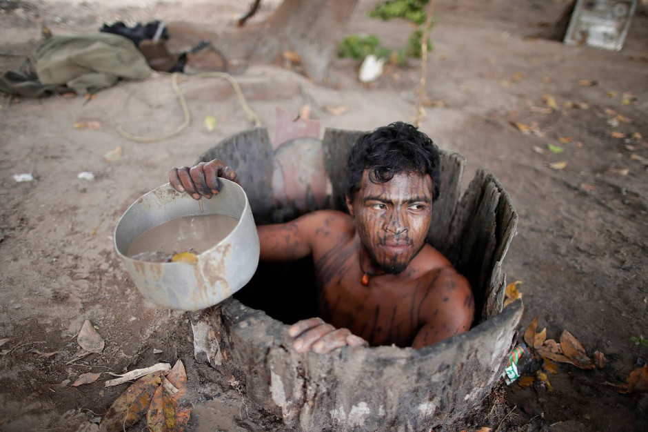 """Ein indigener """"Waldwächter"""" schöpft Wasser aus einem Brunnen."""