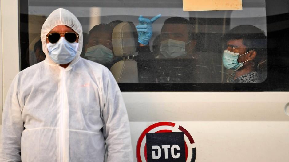 Ein Gesundheitsbeamter steht vor einem Bus, mit dem Corona-infizierte Gastarbeiter in Dubai in die Quarantäne gebracht werden.