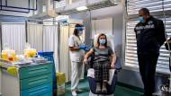 Eine medizinische Angestellte verabreicht einer Frau in einem Mailänder Krankenhaus eine der ersten Corona-Impfungen.