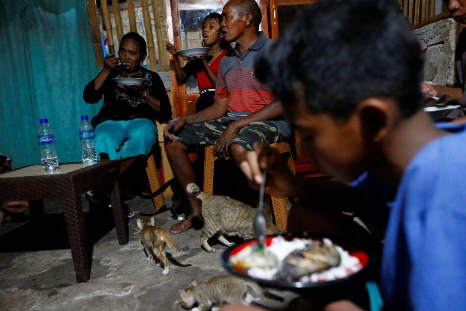 Thomas Tay Ranjawali isst mit seinen Familienmitgliedern Maria Babang Noti, Arini Tenga Lunga und Andreanus Talu Amah in ihrem Haus im Dorf Hamba Praing.
