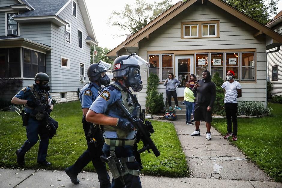 St. Paul, Minnesota am 28. Mai 2020: Polizisten marschieren in Kampfausrüstung auf, Anwohner schauen zu, John Minchillo drückt im richtigen Moment auf den Auslöser.