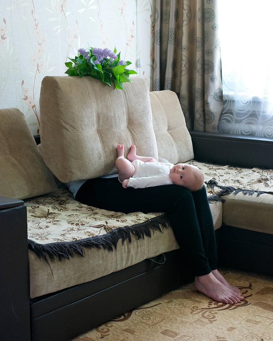 Alena Zhandarova aus Russland ließ sich von der viktorianischen Ära gängigen Praxis inspirieren, bei der kleine Kinder, die für die Kamera posierten, von ihren verdeckten Müttern still gehalten. Indem sie diese Praxis in ihren Fotografien nachbildet, kommentiert Zhandarova den sozialen Status von Müttern, die sich neben ihren Kindern oft unsichtbar oder zweitrangig fühlen.